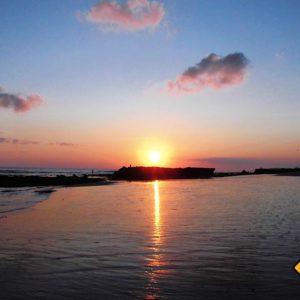 In Canggu geht die Sonne über dem Meer unter und hüllt Strand und Meer in ein faszinierendes Farbspektrum
