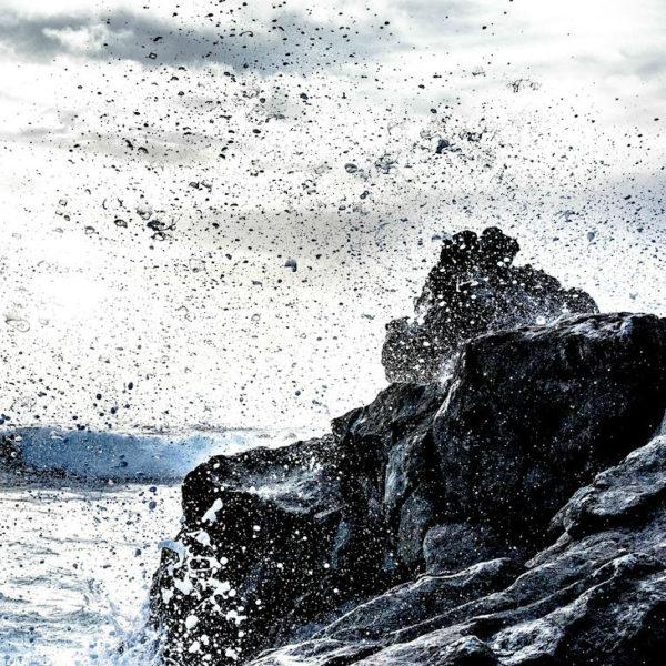 Das Wasser spritzt je nach Wellengang an den Felsen des Playa Montaña Bermeja hervor
