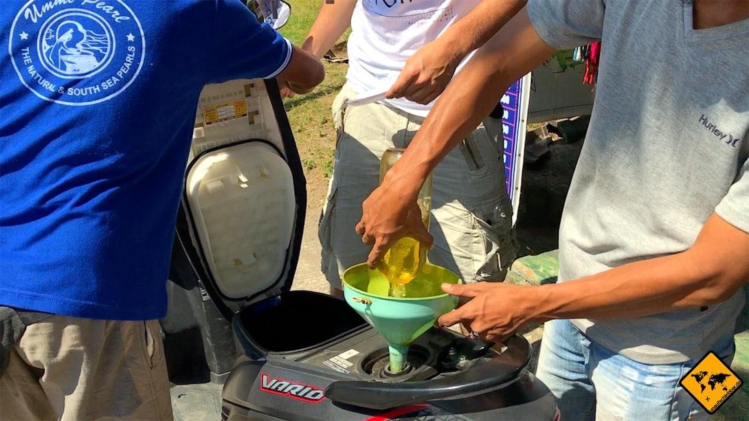 Roller werden auf Bali häufig mit Benzinflaschen und Trichtern am Straßenrand getankt